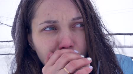 cold : girl freezing wind blows with snow in face, tries to warm hands with her breath