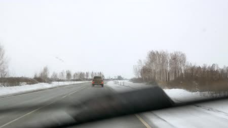 icy : snowstorm on the highway from the window of the car dangerous road icy-hazardous. overtaking on an extreme road Stock Footage