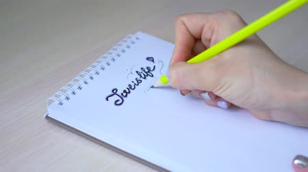 outline : The girl writes the inscription in pencil on a sheet of notepad Love is life Stock Footage