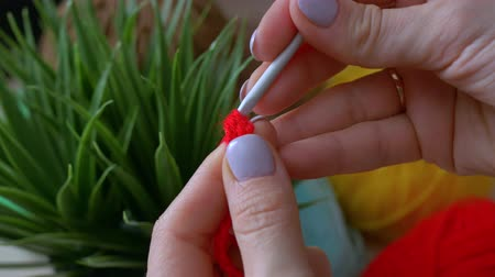 crochê : Handmade crochet close-up. The girl makes the first knots crocheted red color.