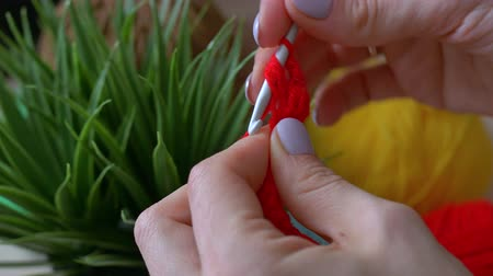 meada : Handmade crochet close-up.The girl knits with red crochet threads.