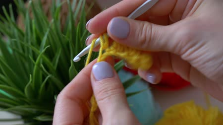 meada : Handmade crochet close-up. Girl learns to crochet with yellow thread.