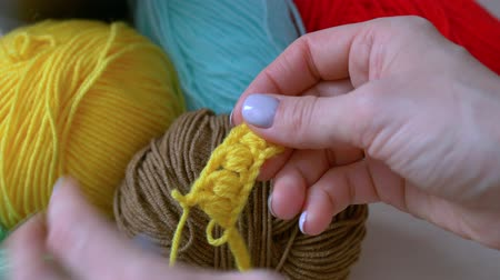 meada : Handmade crochet close-up.girl dismisses the crochet yellow thread Stock Footage