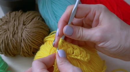 домохозяйка : Handmade crochet close-up. girl crochets with colored threads