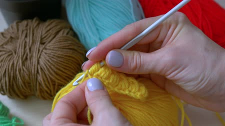 meada : The girl learns to crochet yellow thread.Handmade crochet close-up.