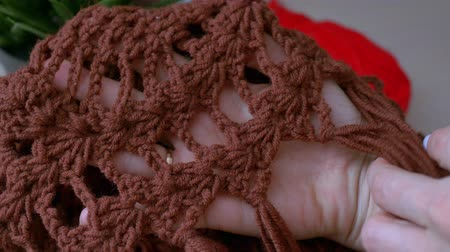 crochê : girl looking at a crocheted lace on a brown scarf. Handmade crochet close-up.