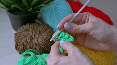 meada : Handmade crochet close-up. girl crochets with green threads