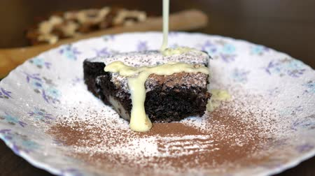 a piece of chocolate cake on a plate, poured with sweet cream