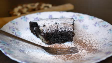 powdered : chocolate piece of cake with icing sugar on a plate sprinkled with cocoa for decoration