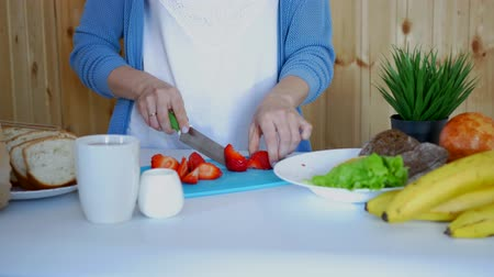 Mom prepares breakfast slices delicious fresh strawberries Stock Footage