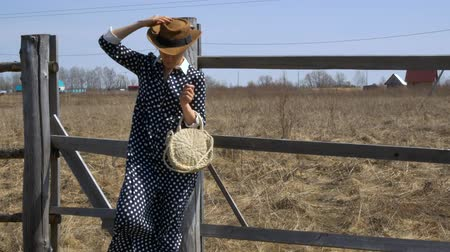 Pretty girl in a hat and straw handbag standing near the fence on a windy day