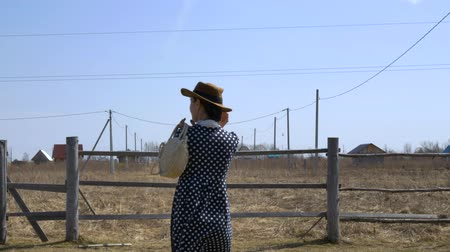 tasje : Pretty girl in a hat and white straw handbag near the fence on a windy day. view from the back