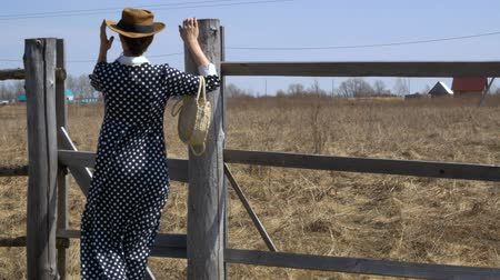 Pretty girl in a hat and white straw handbag standing near the fence on a windy day