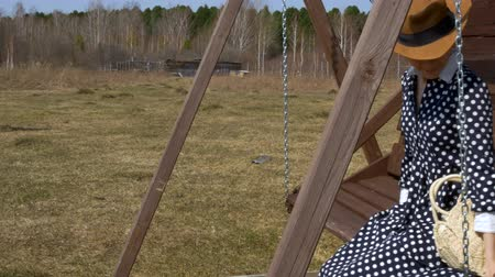 girl in a straw hat sits on a wooden swing in the background of the forest Stock Footage