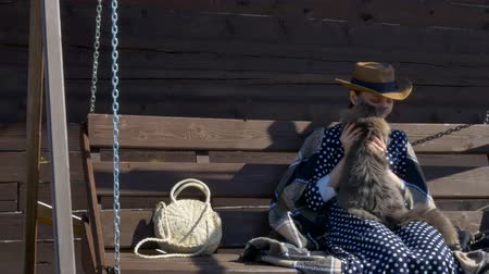 girl in a hat resting on a wooden swing in the village with a fluffy cat Stock Footage