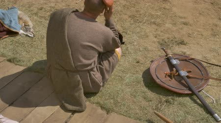 historical reconstruction : A medieval warrior sits on the field, next to a shield is a sword and helmet.