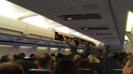 steward : Passengers stack their luggage before the flight in the cabin of the plane.
