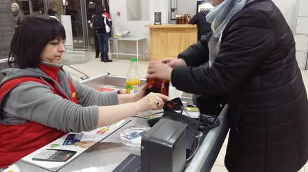 Kiev, March 6, 2018, Ukraine. The cashier in the store. The girl is calculated for the goods by credit card Stock mozgókép