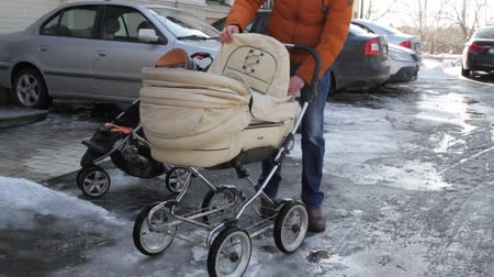 A man takes a bottle of water from a baby carriage.