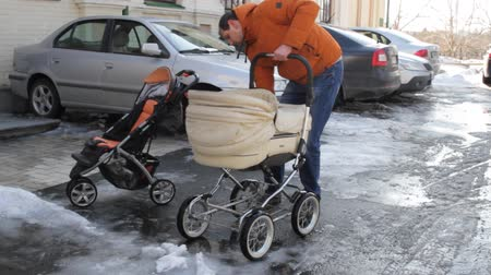 Kiev, 24 March 2018, Ukraine. The man folds the baby carriage and puts it in the trunk of the car.