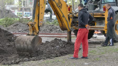 погрузчик : Kiev, 19 April 2018, Ukraine: The bucket of the excavator digs the ground Стоковые видеозаписи
