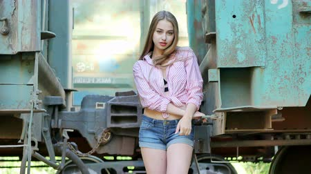 emissão : Beautiful girl posing between railway