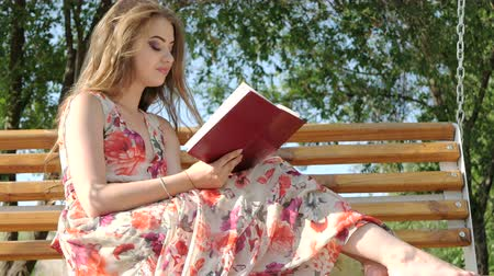 Girl with a book on a bench in the park Stock Footage