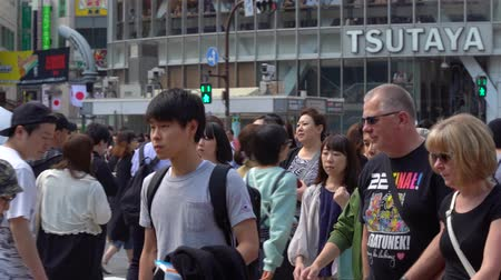 Tokyo, Japan-May 4, 2019: Close up pedestrians walking on Shibuya Crossing in day time (Slow Motion Video). Camera panning right to left, selective focus