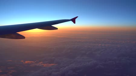 view of aircraft wing silhouette in dark blue sky horizon and cloud background in sun rise time. Стоковые видеозаписи