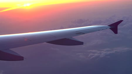 Up in the air, view of aircraft wing silhouette in dark blue sky horizon and cloud background in sun rise time. from viewed airplane window, with a reflection camera lens Dostupné videozáznamy