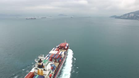 damarlar : Amazing 4k aerial view on a cargo freight ship sailing slowly in the ocean on a cloudy day Stok Video