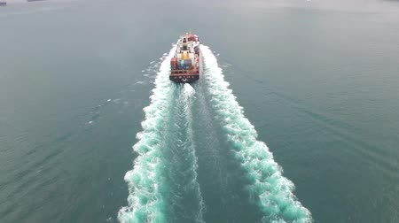 eau : Freight cargo ship sails slowly in the ocean waves on a cloudy foggy day in 4k aerial shot Stock Footage