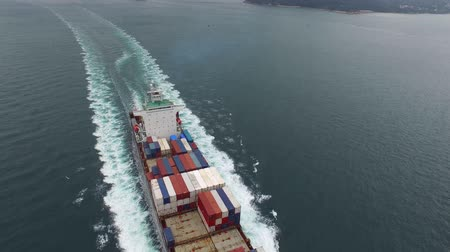 eau : Freight container ship sails in the ocean waves on a cloudy day in 4k aerial shot Stock Footage
