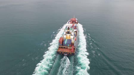 eau : Container freight ship sailing in the calm ocean waves on a cloudy day in 4k aerial shot
