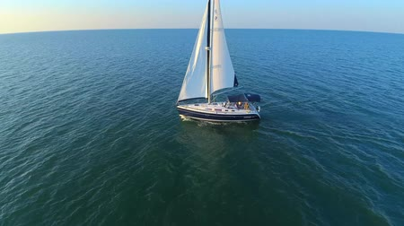 żaglówka : Lonely boat yacht sailing slowly in calm open sea in evening sunset in 4k aerial Wideo