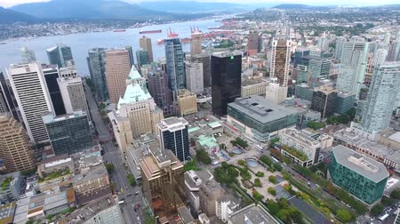 skyscraper : Vancouver downtown financial district big famous modern skyscrapers towers architecture by water in 4k aerial panorama Stock Footage