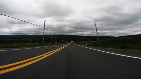 longboarder : Man skateboarder skating fast downhill the countryside suburban road on longboard on cloudy day in low angle 4k shot