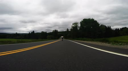 longboarder : Professional skateboarder skating fast downhill the empty countryside road on longboard on cloudy day, low angle 4k shot