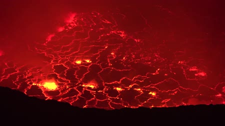 erupt : Melting lava lake erupting and flowing at Nyiragongo volcano crater in Congo Africa in 4k aerial shot at night time