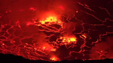 erupt : 4k aerial close up shot of melting lava erupting at active Nyiragongo volcano crater lake in Congo Africa at night time