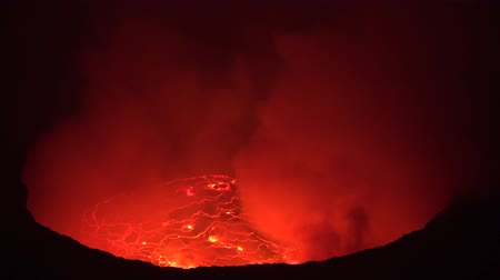 rachaduras : Spectacular 4k view on huge red erupting lava lake with volcanic gas at active Nyiragongo volcano in Congo at night