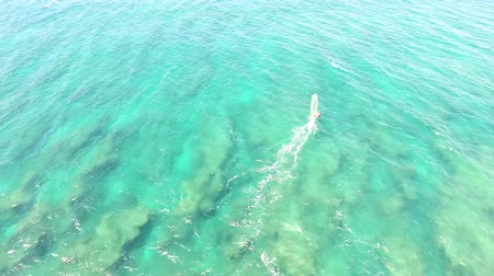 tyrkysový : Top 4k aerial veiw on professional windsurfer surfing in calm turquoise blue ocean water in extreme summer sport skyline