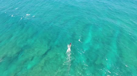 tyrkysový : Amazing 4k top aerial drone camera seascape view on windsurfer gliding slowly in calm turquoise blue tropic ocean water