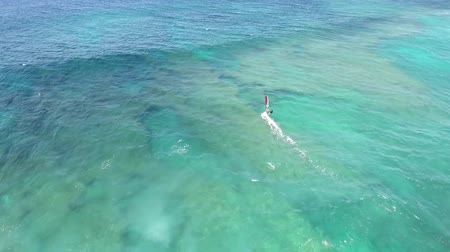 tyrkysový : 4k aerial drone view of professional windsurfer gliding in calm waves of turquoise blue ocean water Hawaiian seascape