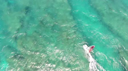 bezmotorové létání : Professional windsurfer gliding in calm waves of turquoise blue ocean water Hawaiian seascape in top 4k aerial drone cam