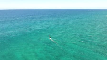 bezmotorové létání : Windsurder gliding slowly in calm waves of turquoise blue Pacific ocean water Hawaii in amazing 4k aerial drone seascape