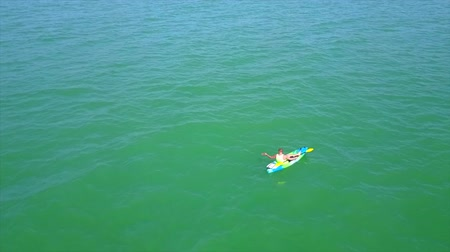 kano : 4k aerial drone seascape of kayaker in diving kayak, extreme summer water sport activity ecotourism blue empty open sea