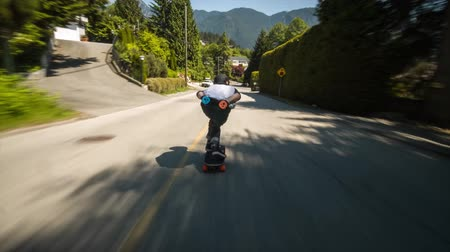 longboarder : 4k first person pov of professional skateboarder skating fast downhill the countryside lane through forest on longboard Stock Footage