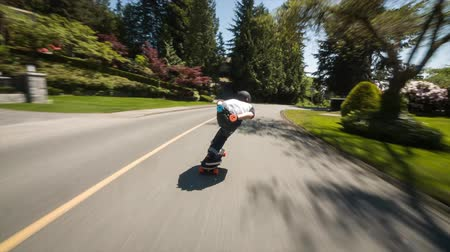 longboarder : 4k first person pov of professional skateboarder skating on longboard skate extreme fast downhill the countryside lane