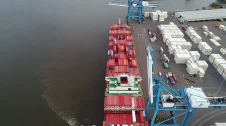sending : 4k aerial shot on a huge red cargo freight container ship loading at industrial urban port harbor on cloudy day